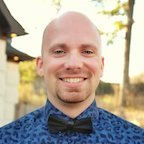 Taylor Otwell looking happy in a swag blue shirt and bowtie